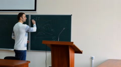 High white student diligently wipes the blackboard with a damp cloth - stock footage