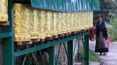 Tibetan people turning the prayer wheels at temple in Dharamsala, India - stock footage
