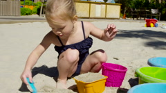 Young Girl plays in sand with shovel and bucket at pool resort Stock Footage