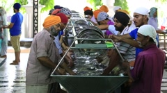 Poor indian people wash dishes in Sikh Golden Temple, Amritsar. India Stock Footage
