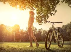 Woman under sun light at day near her bicycle in the park - stock photo