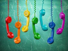 Telephone receivers of different colors hanging on the green background. Commu Stock Illustration