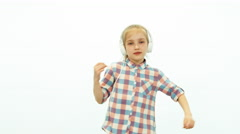 Child girl listening music and dancing on the white background - stock footage