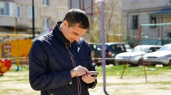 Man with smartphone dials the message close-up sunlight Stock Footage