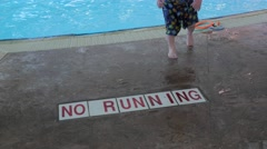 No running sign on the floor at the pool with kids feet going by. - stock footage