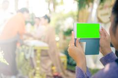 People use smart phone to take photographs in Thai wedding ceremony. (green s Stock Photos