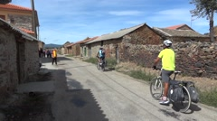 Group of cyclists and pilgrims who walk through the stone walls that guard the - stock footage