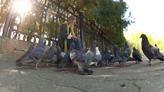 Beautiful girl feeding pigeons in the park Stock Footage
