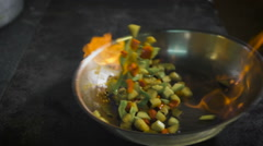 Chef frying vegetables. Cognac is ignited in the pan. Open fire in the kitchen Stock Footage