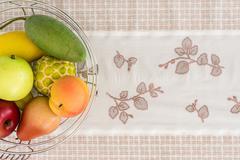 Artificial fruit on patterned fabrics. Stock Photos