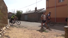 Group of cyclists and pilgrims that pass a group of local exit from church Stock Footage
