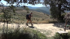 Traveler carrying a backpack and two ski sticks go on a path besides a resting Stock Footage