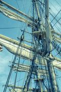 Sails and tackles of a sailing vessel on a background of the sky - stock photo