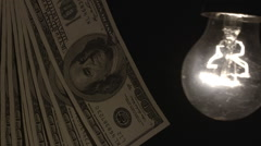 Hanging light bulb dangle on a wire illuminating bank notes - stock footage