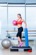 Fitness girl, wearing in sneakers, red top and black  breeches, posing on step Stock Photos