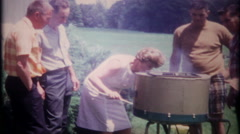 3216 housewife helps the men with the barbecue grille -vintage film home movie Stock Footage