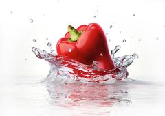 Red sweet bell pepper falling and splashing into clear water. Stock Illustration