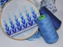 Detail of embroidery products with blue thread in wooden hoop - stock photo