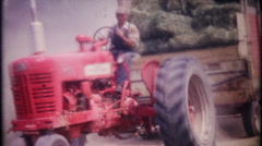 Stock Video Footage of a farmer harvesting hay, then conveyer belt to loft - vintage film home movie