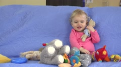 Small girl sitting on sofa and soft toys throw on her Stock Footage