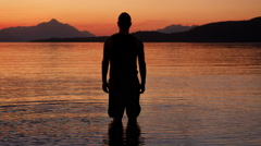 Silhouette of a man at the lake at sunset Stock Footage