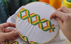 Hoop with retro embroidered on the fabric Stock Photos