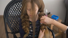 Mom makes hairstyle for a sad little girl - stock footage