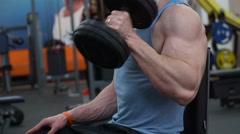 Guy doing lifting dumbbells for biceps Stock Footage