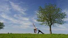 Young flexible woman flows into a yoga wild thing pose or Camatkarasana Stock Footage