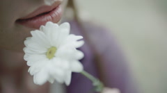 Female leads white flower near her face Stock Footage