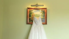 White lace wedding dress hanging on the green wall background. Wedding - stock footage