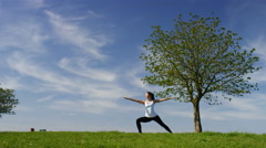 Young woman flows into a yoga warrior pose Stock Footage