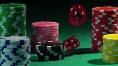 Red dice falling upon stacks of poker chips in slow motion, casino background Stock Footage