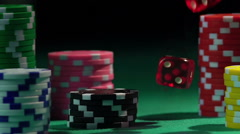 Stacks of chips on green poker table, throwing dice in slow motion. Gambling Stock Footage