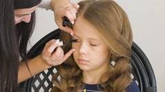 Unhappy little girl. Mom or barber braids her braids. Brown hair Stock Footage