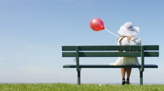4K Female in a sun hat sitting on a bench, holding a red balloon Stock Footage