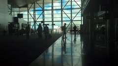 Silhouettes of people walking around in airport terminal. Stock Footage