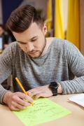 Cheerful young guy is studying with concentration - stock photo