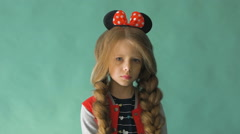 Little girl with braids and a bow in her hair. Posing in the studio Stock Footage