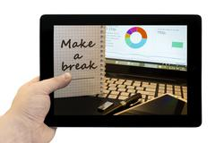 Tablet PC in hand with inscription - Make a break in notepad on office workin Stock Photos