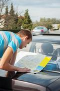 Traveler searching the routes on the map bended to car - stock photo