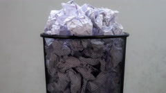 An empty office trash basket gets filled up with waste papers. Stop motion Arkistovideo
