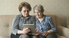Two elderly women watch pictures using a tablet Stock Footage
