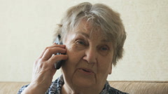 Old woman talking on a mobile phone Stock Footage