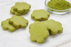 Homemade matcha green tea shortbread cookies on parchment - stock photo