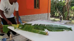 Artist arranging banana leaves on a canvas Stock Footage