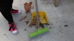 (Close up) Leaves and debris being swept into dust pan Stock Footage