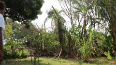 Woman walking through yard to banana trees Stock Footage
