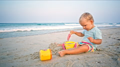 Toddler boy plays sand toys on the beach Stock Footage