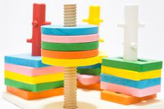 Colorful puzzle wooden toy on white table - stock photo